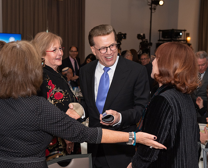 29th Awards Luncheon Patty Tanner (JEA '18, right) and Ofra Dor (JEA '96) talk with Lowell Milken, chairman and co-founder of the Milken Family Foundation.