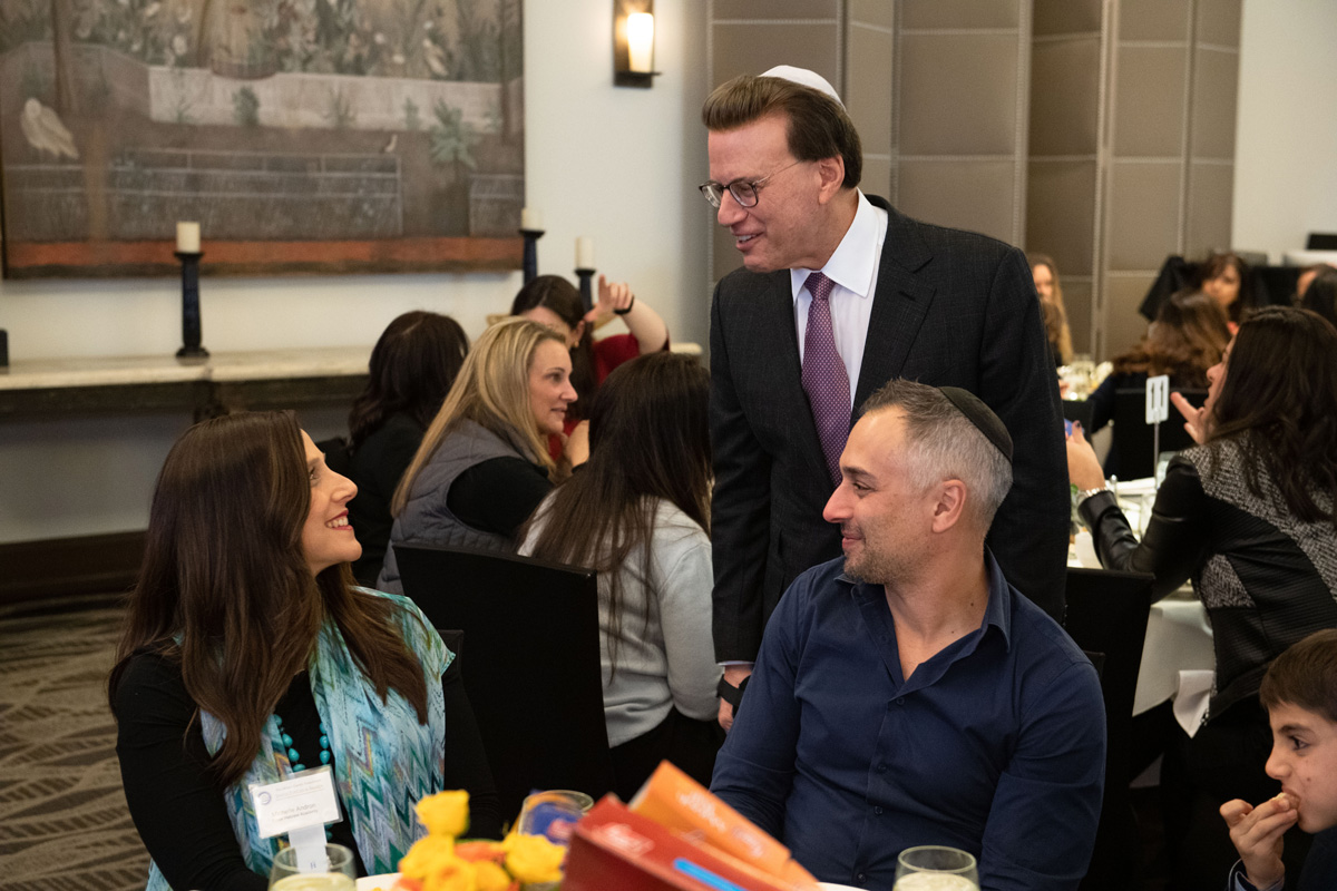 30th Awards Luncheon Lowell Milken, chairman and co-founder of the Milken Family Foundation, talks with 2019 Jewish Educator Award recipient Michelle Andron and her family before the presentations begin.